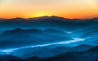 Golden sunset light above the blue foggy mountain valley wallpaper
