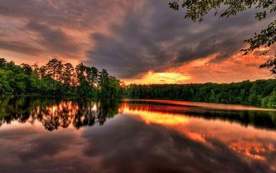 Golden sunset reaching through dark clouds reflecting in the lak wallpaper