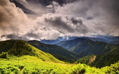 Green forest mountains aspiring to the fluffy clouds Wallpaper