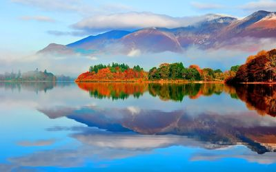 Lake reflecting the cloud covered mountains Wallpaper
