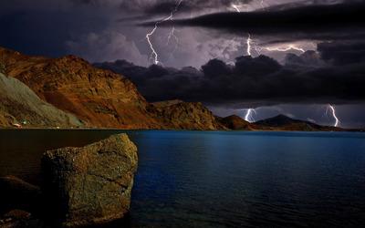 Lightnings over the rocky shore wallpaper