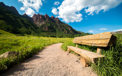 Log bench on the path to the mountains wallpaper