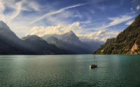 Lonesome small boat on the lake surrounded by the mountains wallpaper 1920x1200 jpg
