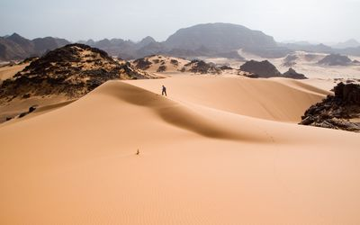Man walking on the sand dune wallpaper