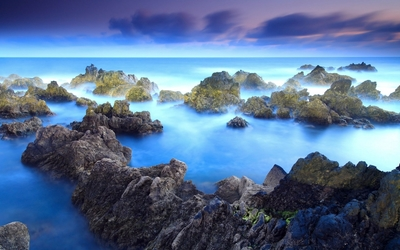 Mossy rocks rising from the amazing blue ocean wallpaper