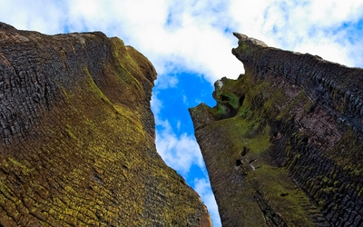 Mossy rocky peaks rising towards the clouds wallpaper