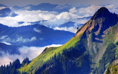 Mountain tops mixing with the clouds Wallpaper
