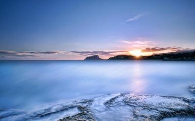 Ocean sunset behind the rocky shore Wallpaper