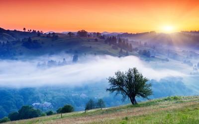 Orange sunset over the foggy valley wallpaper