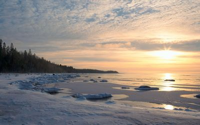 Peaceful sunset over the frozen land by the ocean wallpaper