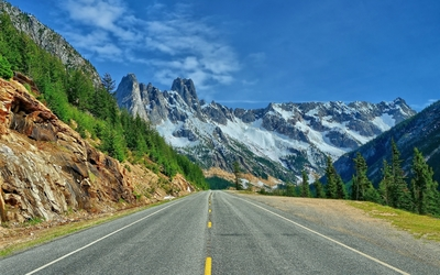 Road towards the snowy mountain peaks wallpaper