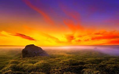 Rock rising from the grass to the gorgeous sunset wallpaper