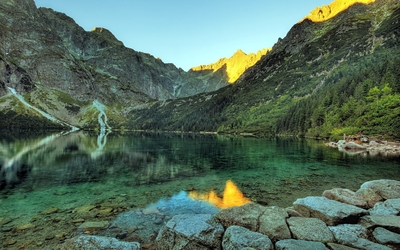 Rocky lake by the forest mountain Wallpaper