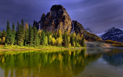 Rocky peak standing tall above the forest by the lake wallpaper