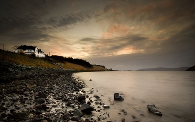 Rocky shore at the lake on a clouded day wallpaper