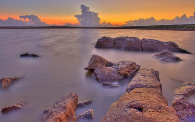 Rusty rocks in the water guarding the beautiful sunset light wallpaper