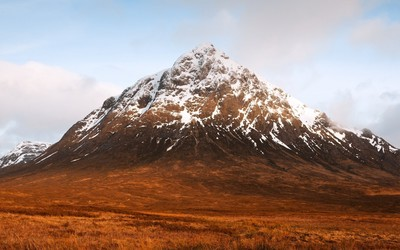 Rusty, rocky and snowy mountain peak Wallpaper