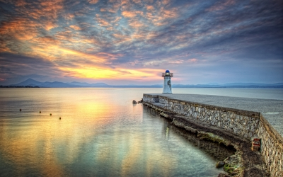 Small old lighthouse on a stone pier wallpaper