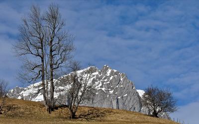 Snow on rocky mountain hill Wallpaper