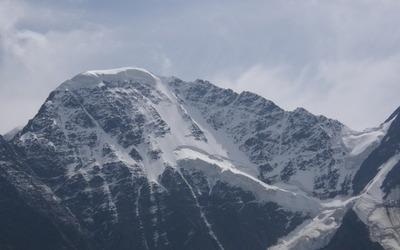 Snow on rocky mountain peak wallpaper