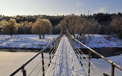 Snowy narrow bridge across the frozen river wallpaper