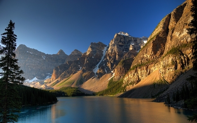 Sun warming up the rocky mountain peaks by the river wallpaper