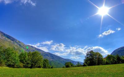 Sunlit mountain field wallpaper