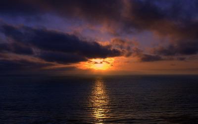 Sunset light piercing through dark clouds wallpaper