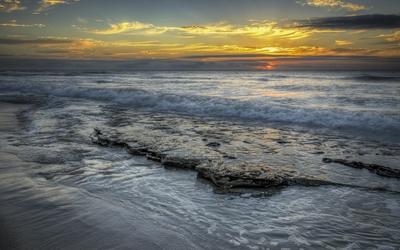 Sunset over the wavy ocean wallpaper