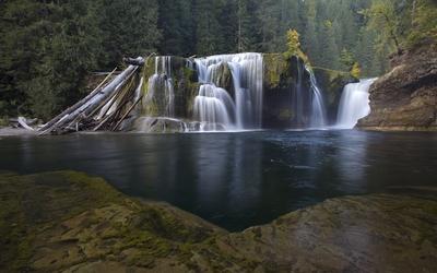 Water falling between mossy rocks wallpaper