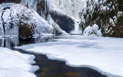 Waterfall on frozen river in the rocky mountains wallpaper