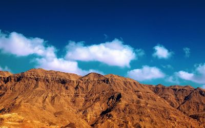 White fluffy clouds above the arid hills Wallpaper