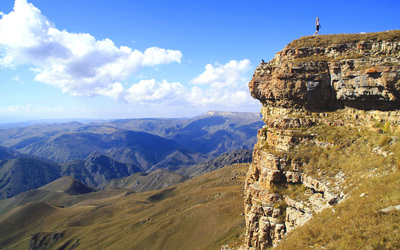 Woman on top of the mountain cliff Wallpaper
