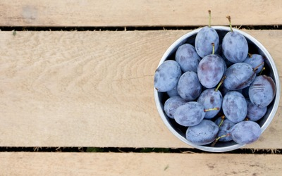 Bowl of plums on wood wallpaper