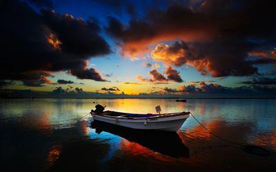 Burning clouds between dark ones above the boat wallpaper