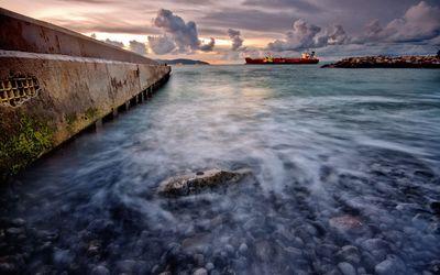 Cargo boat near the rocky shore wallpaper