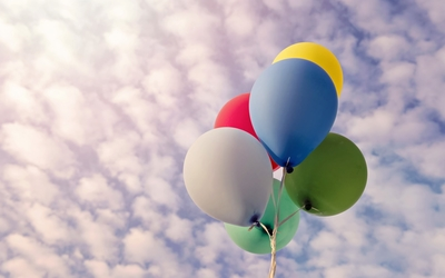 Colorful balloons rising to the fluffy clouds wallpaper