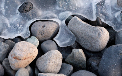 Frozen waves around the pebbles wallpaper