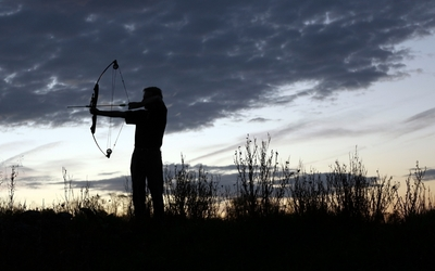 Man shooting with arrow at sunset wallpaper