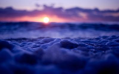 Purple sunset light on foamy waves wallpaper