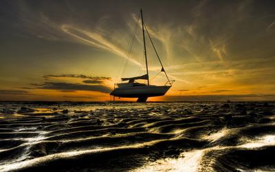 Sailboat on a sunset sandy beach Wallpaper