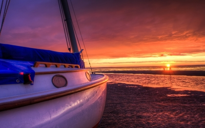 Sailing boat on a sunset beach Wallpaper