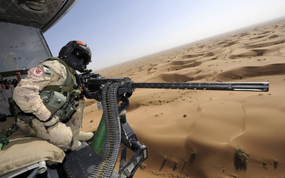 Soldier operating a machine gun in a helicopter wallpaper