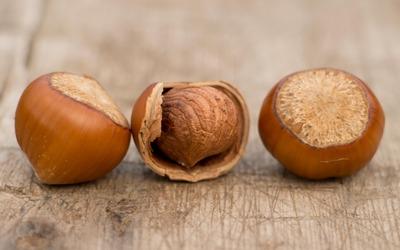 Three hazelnuts on wood wallpaper