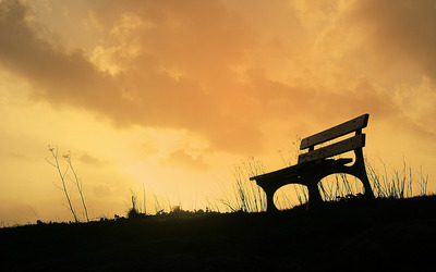 Watching the sunset from a wooden bench Wallpaper