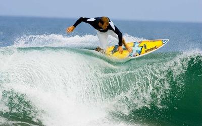 Surfer riding a foamy wave wallpaper