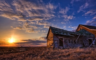 Amazing sunset sky above the forgotten house on the field wallpaper