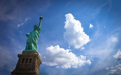 Fluffy clouds above the Statue of Liberty wallpaper