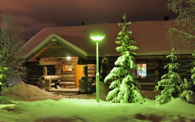 Green lamp on snowy trees wallpaper
