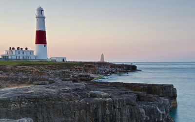 Lighthouse on top of the rocky shore wallpaper